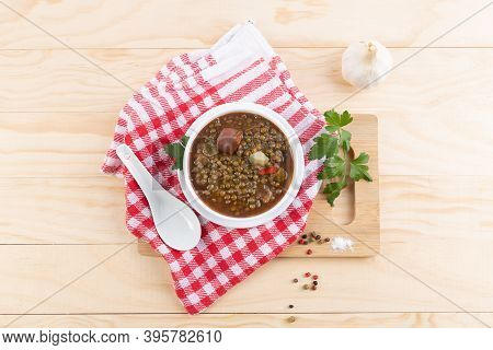 Traditional Spanish Dish Of Lentil Stew With Chorizo And Potatoes, On A Light Wooden Base. Flat Lay