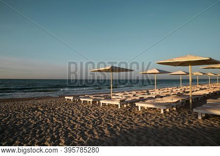 Blue Sky And Sea Beach With Sun Umbrellas And Chaise Lounges On Sandy Natural Background. Summer Vac