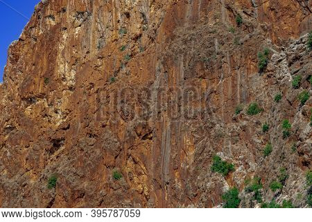 Steep Cliff Of High Mountain, Close-up. Texture Of Brown-orange Rock With Sparse Green Plants On It