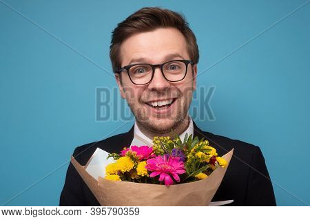 Smiling Man Holding A Bouquet Of Flowers Making A Proposal.
