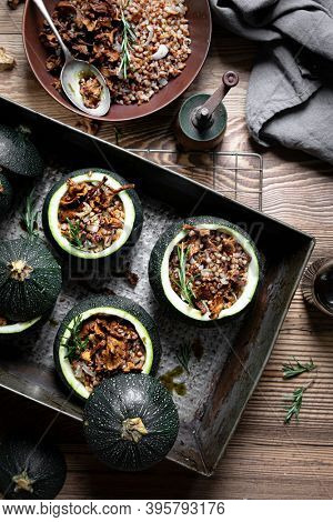 Delicious chanterelle stuffed round zucchini on wooden table