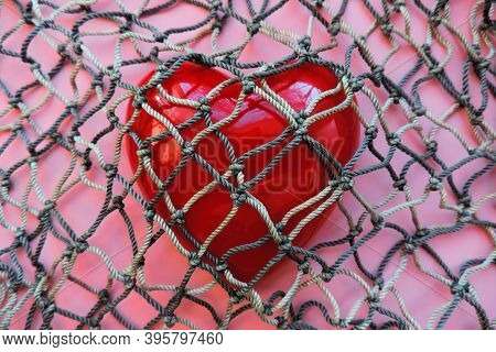 Red Heart Covered With Mesh. Concept Of Rejection Of Love, Prohibition Of Free Expression Of Emotion