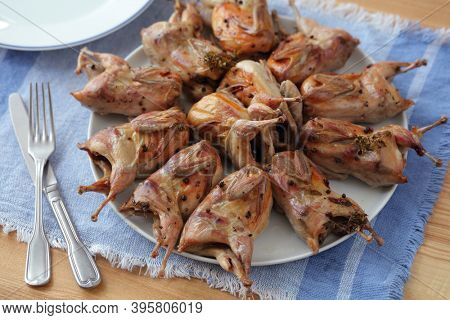 Roasted quails seasoned with red peppercorns in a big round dish on a table