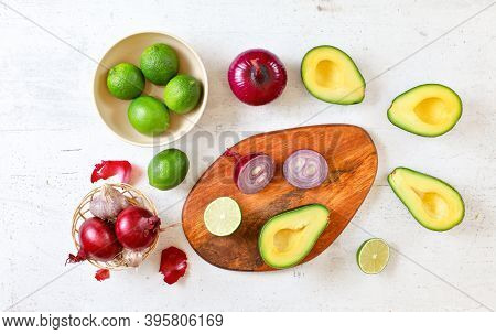 Avocado Halves, Limes And Onions - Basic Guacamole Ingredients On White Working Board, Flat Lay Phot