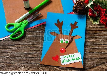 Merry Greeting Card With A Christmas Deer On A Wooden Table. Handmade. Children's Creativity Project