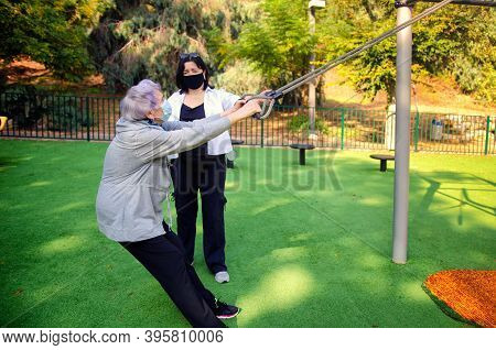 A Physical Therapist Or Caretaker Watches Attentively As An Old Woman Training On An Outdoor Fitness