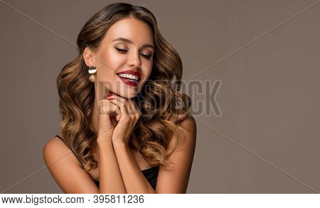 Beautiful Smiling Woman With Long Wavy Hair .  Girl Curly Hairstyle  And Red Manicure Nails . Beauty