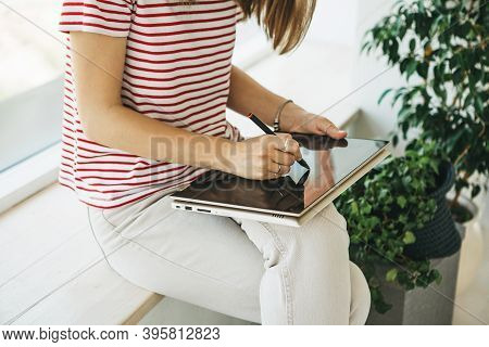 Girl Digital Artist Draws With A Stylus On A Tablet Or Laptop. She Is A Student And Is Studying Draw