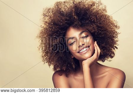 Beauty Portrait Of African American Woman With Clean Healthy Skin On Beige Background. Smiling Beaut