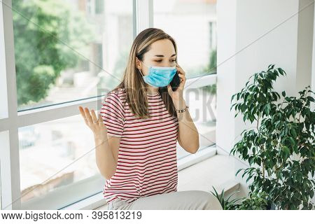 A Girl In A Medical Protective Mask Is Talking On The Phone.