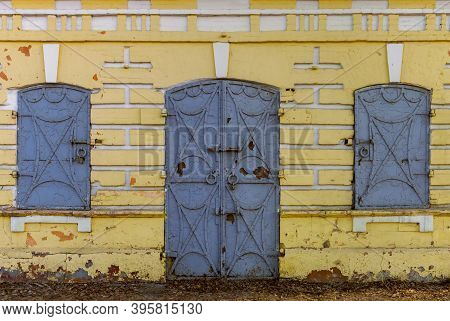 Old Yellow Wall With Iron Door And Window Shutters