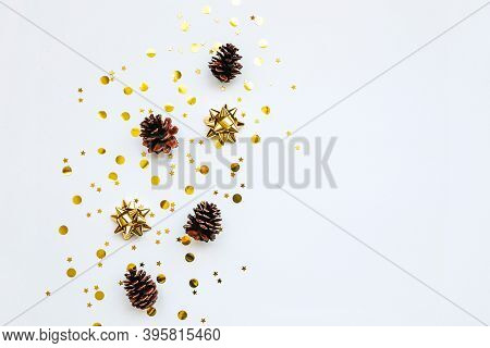 Festive Golden Bows And Cones On A White Background With Confetti. Christmas Or New Year Background.