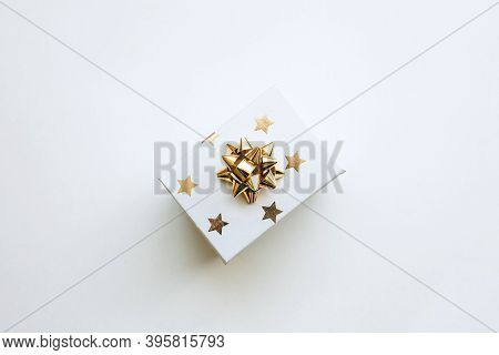 Gift Box With A Gold Bow On A White Background In A Minimal Style. Festive Concept.