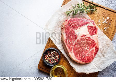 Raw Fresh Meat Ribeye Steak And Seasonings On Light Background, Top View With Copy Space