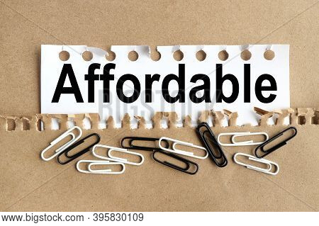 Affordable, Text On White Paper Over Torn Paper Background.