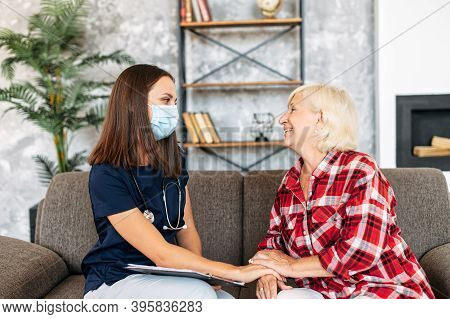 Doctor In Protective Medical Mask Visits Her Senior Patient At Home. Therapist Is Taking A Notes, A