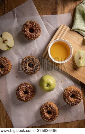 Baked Apple Cider Donuts With Apples, Cider And Textile Napkin On Baking Sheets On Natural Wooden Ta