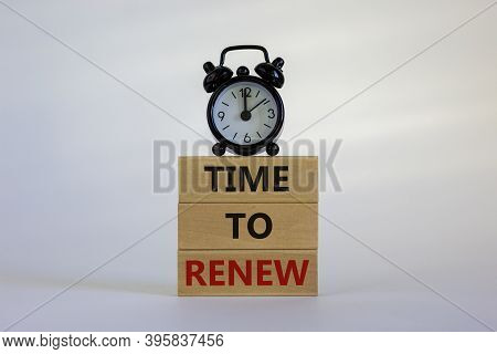 Wooden Blocks With Words 'time To Renew'. White Table. Black Alarm Clock. Beautiful White Background