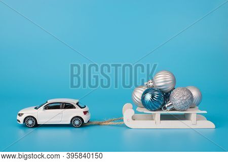 Christmas Celebration Concept. Close Up Photo Of Toy Mini Car Carrying White Wooden Sledge With Litt