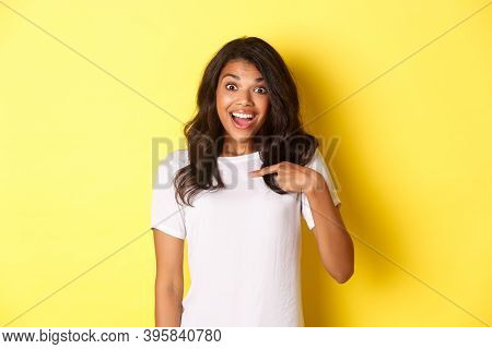 Image Of Attractive African-american Girl Looking Amazed And Happy, Smiling While Pointing At Hersel