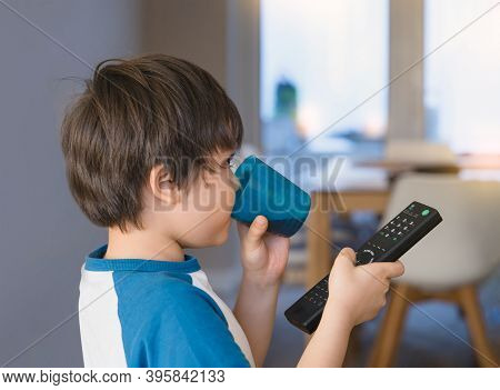 Kid Drinking Soda Drink In Plastic Glass And Holding Remote Control, Asian Young Boy Having Fun Drin