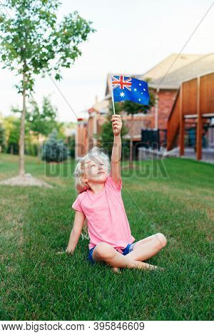 Happy Caucasian Blonde Girl Holding Australian Flag. Smiling Child Sitting On Grass In Park Waving A