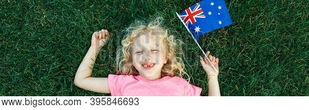 Adorable Cute Happy Caucasian Girl Holding Australian Flag. Smiling Laughing Child Lying On Grass Wi