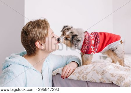 Young Woman With Short Hair Kissing Cute Puppy Dog At Home. Pet Owner With Little Furry Friend. Smal