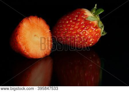 Whole And Split Strawberry On Black Background And Base With Reflections Enviar Comentarios Historia