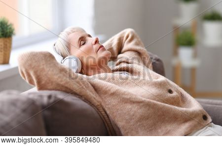 Elderly Lady In Headphones Lying On Couch And Listening To Music With Closed Eyes While Resting In C