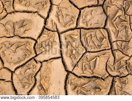 Cracked Dry Brown Earth, Dry Earth Surface, Abstract Textured Background. Dehydrated Land, Drought.