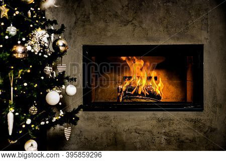 Dark Wall With Dark Christmas Tree With Shining Fireplace And White Christmas Decoration