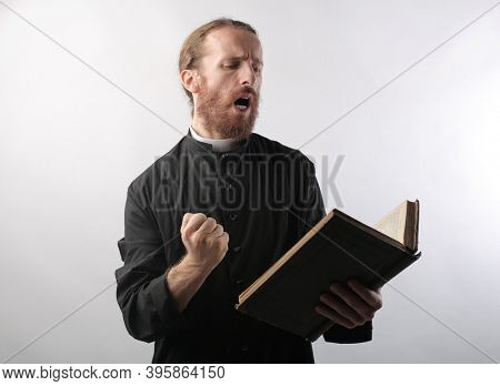 portrait of a young priest while reciting bible verses