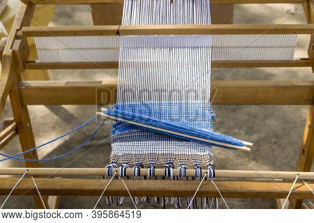 Blue Wool Being Woven Into A Piece Of Fabric On A Manual Loom