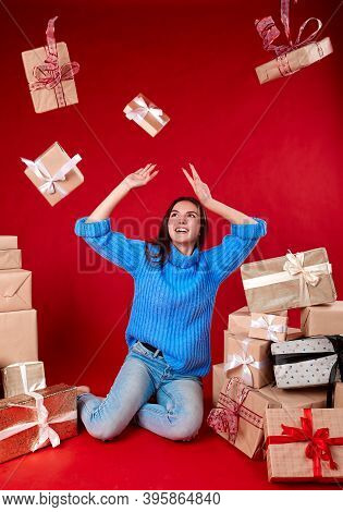Gifts Fly To The Girl From All Sides On A Red Background.