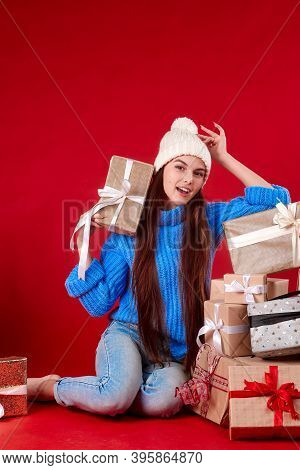 Girl In A Knitted Hat With New Years Gifts On A Red Background.