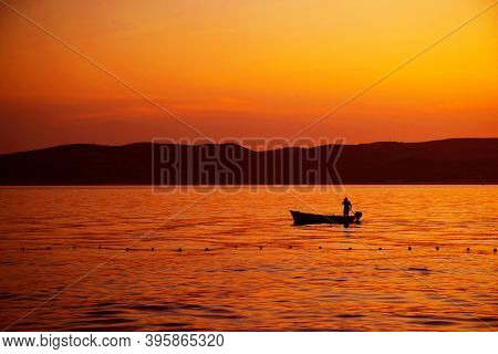 Image of a fishing boat against the sunset background