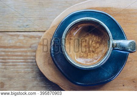 A Cup Of Hot Espresso Shot On The Wooden Table. Espresso Is A Full-flavored It Is Made By Forcing Pr