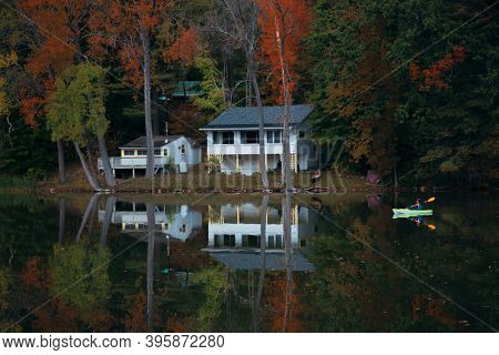 Beautiful Fall colors with house over lake in New England in USA