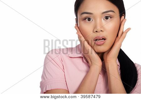 Attracive Asian woman reacting in shock and horror with her eyes wide and hands raised to her cheeks, cropped portrait isolated on white