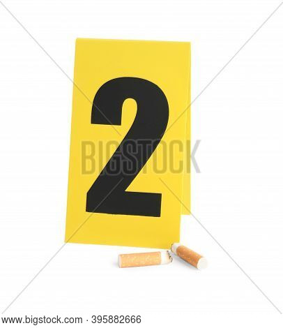 Cigarette Stubs And Crime Scene Marker With Number Two Isolated On White