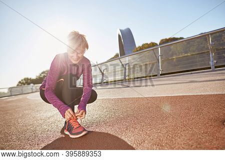 Get Ready. Full Length Shot Of Active Mature Woman Wearing Sportswear Tying Shoelaces On Sporty Snea