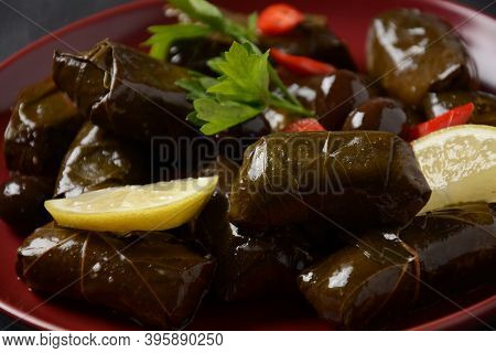 Traditional Greek Cuisine. Wrapped Rice In Grape Leaves. Dolma With Lemon, Spices, Various Pickled O