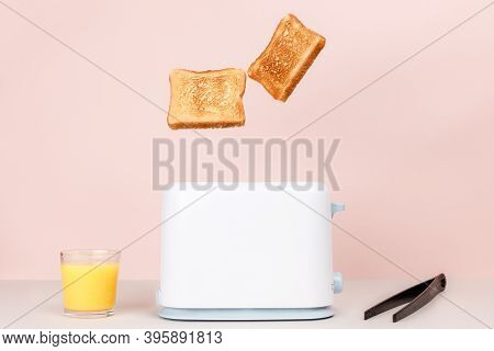 Toasted Bread Flew Out Of White Toaster. Near Glass Of Orange Juice And Tongs For Toast. Levitation