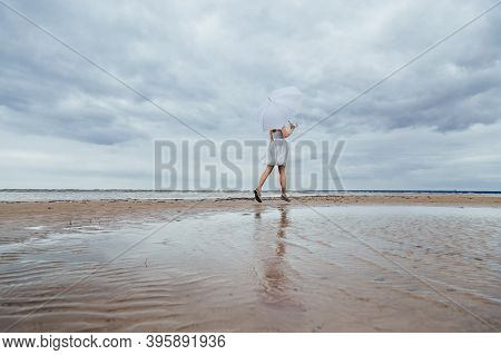 Unrecognizable Pretty Girl In Grey Dress With White Umbrella Runs Along The Sea. A Good Place To Cle