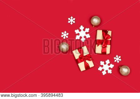 Gifts, White Snowflakes, Golden Decorations Flat Lay On Red Background Top View, Copy Space. Creativ