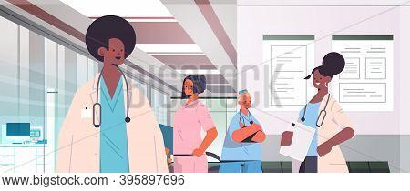 Team Of Mix Race Doctors In Uniform Discussing During Meeting In Hospital Corridor Medicine Healthca