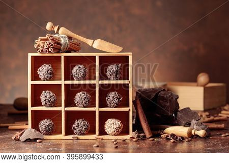 Chocolate Truffles With Broken Pieces Of Chocolate. Chocolate, Spices, And Ingredients On A Brown Ta