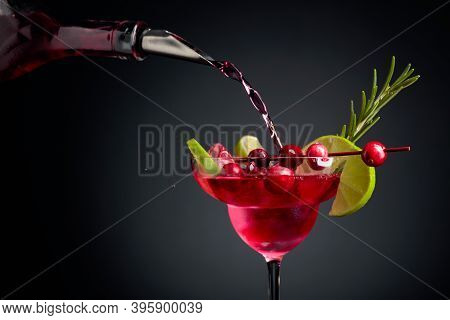 Cranberry Cocktail Garnished With Berries, Lime, And Rosemary. In Frozen Glass With Ice Is Pouring C