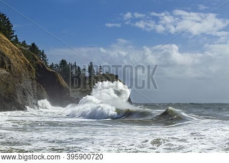 Cape Disappointment Lighthouse On A Cliff Along The Pacific Ocean With A Crashing Wave.